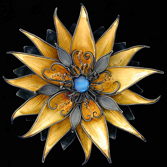 A brooch/pendant made with hand textured sterling silver, gold overlay, granulation, and a blue moonstone cabochon