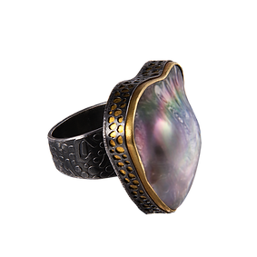 A ring with a wide textured silver band, an abalone mabe pearl, a gold bezel and an outer pierced silver bezel