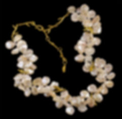 A strand of white petal pearls with 22 karat gold twigs and leaves, with diamonds