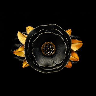 A bangle bracelet with a large silver poppy, gold leaves, and a band made of silver twigs