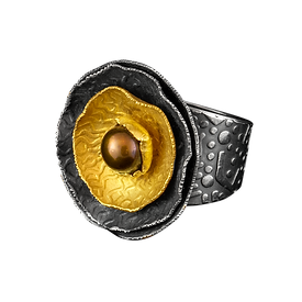 A ring with a textured wide band, with silver and gold textured discs and a copper pearl