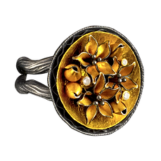 A ring with a twig-like oxidized silver double band, and a gold dish center with gold shaped into flowers and buds, with three diamonds