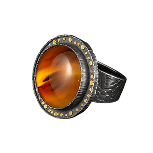 An oxidized sterling silver ring, with a broad textured band, a wide textured bezel with gold circles, and a montana moss agate cabochon