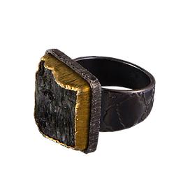 A ring with a square surface tourmaline, a double silver and gold bezel, and a textured silver bezel