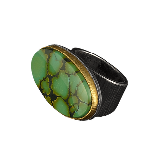A ring with a chinese turquoise cabochon, a double silver and gold bezel, and a textured silver bezel