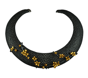 A shagreen collar with a gold and oxidized silver branch with flowers fitted to the front.