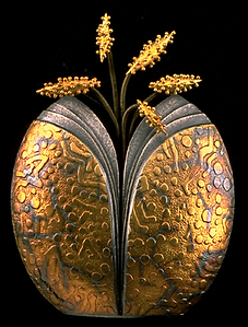 A brooch/pendant with a textured gold overlay hollow form and gold granulation