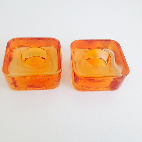 Porta velas em formato quadrado cor laranja.
