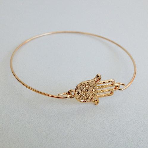 Pulseira dourada com pingente Hamsa.
