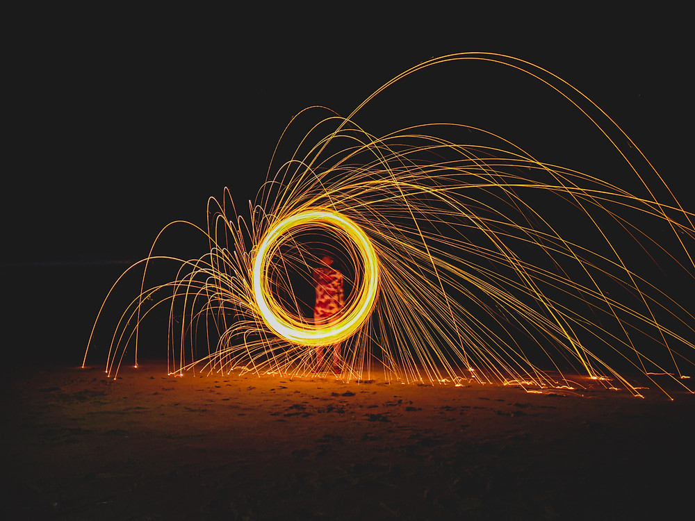 Steel Wool Photography is using long exposures to capture the motion of hot embers flying through the air through the act of spinning burning steel wool. These embers are so hot that they glow very brightly,