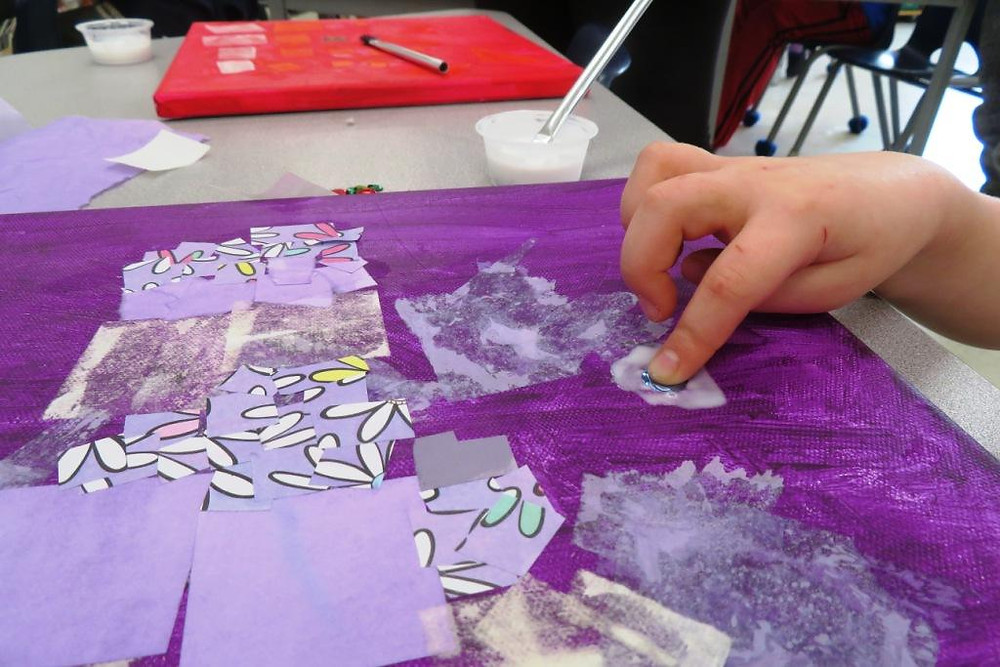 Students adding sequins and coloured paper onto thier canvases