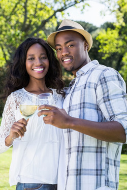 Portrait of young couple toasting glasses of wine in the park