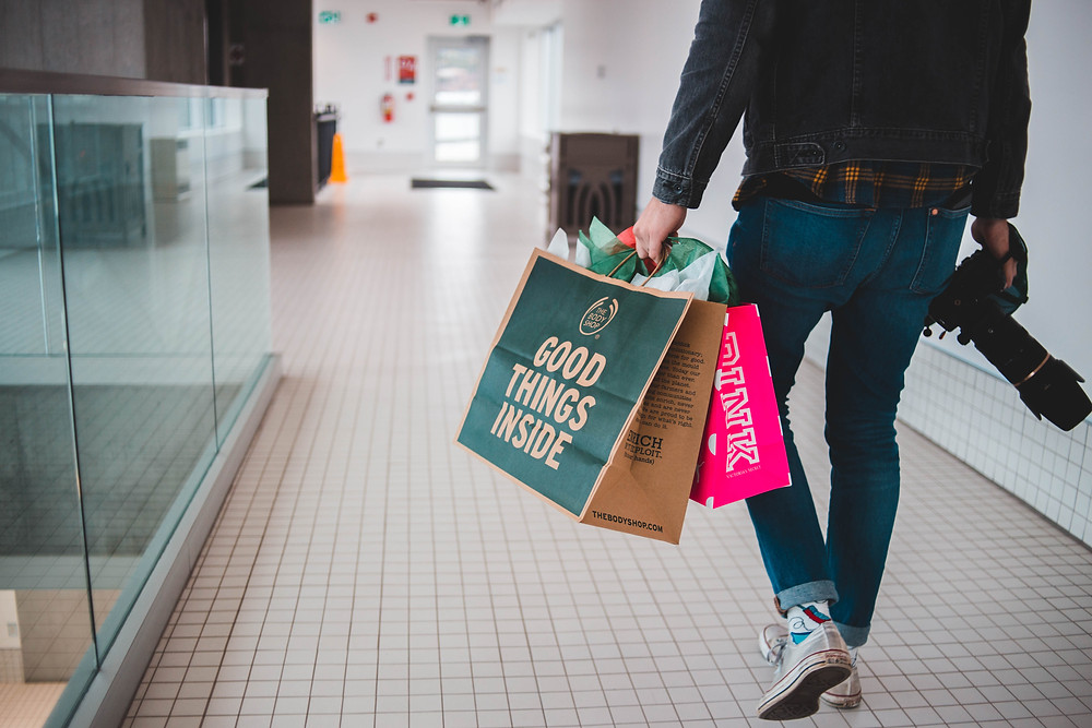 Man in denim walking with camera and shopping bags