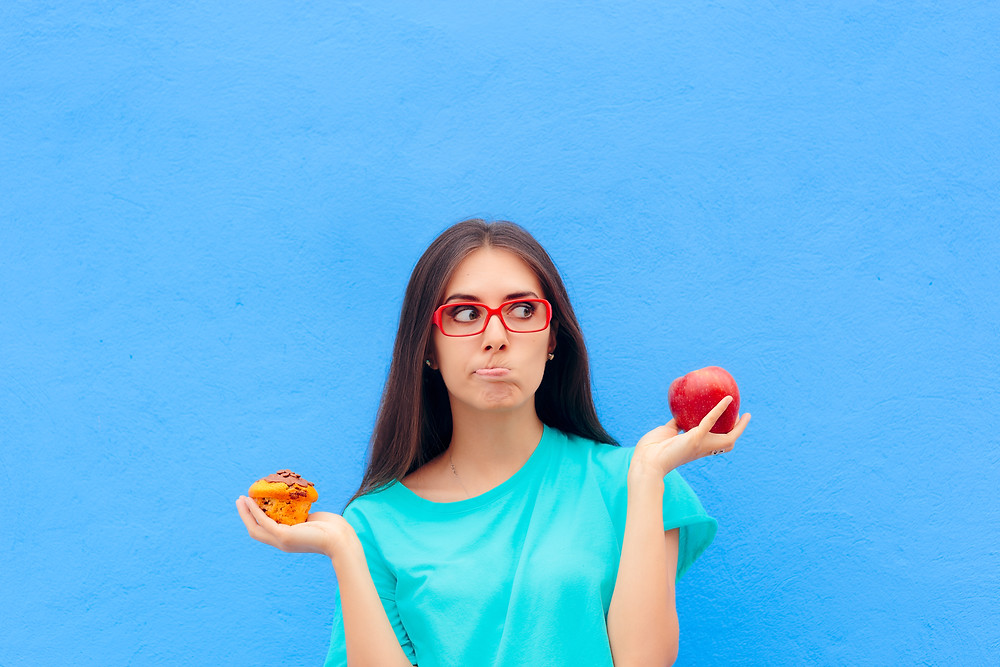 girl weighing up a muffin and an apple