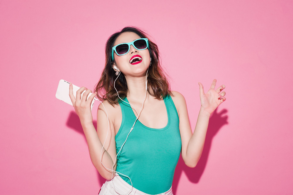 girl listening to music with pink background