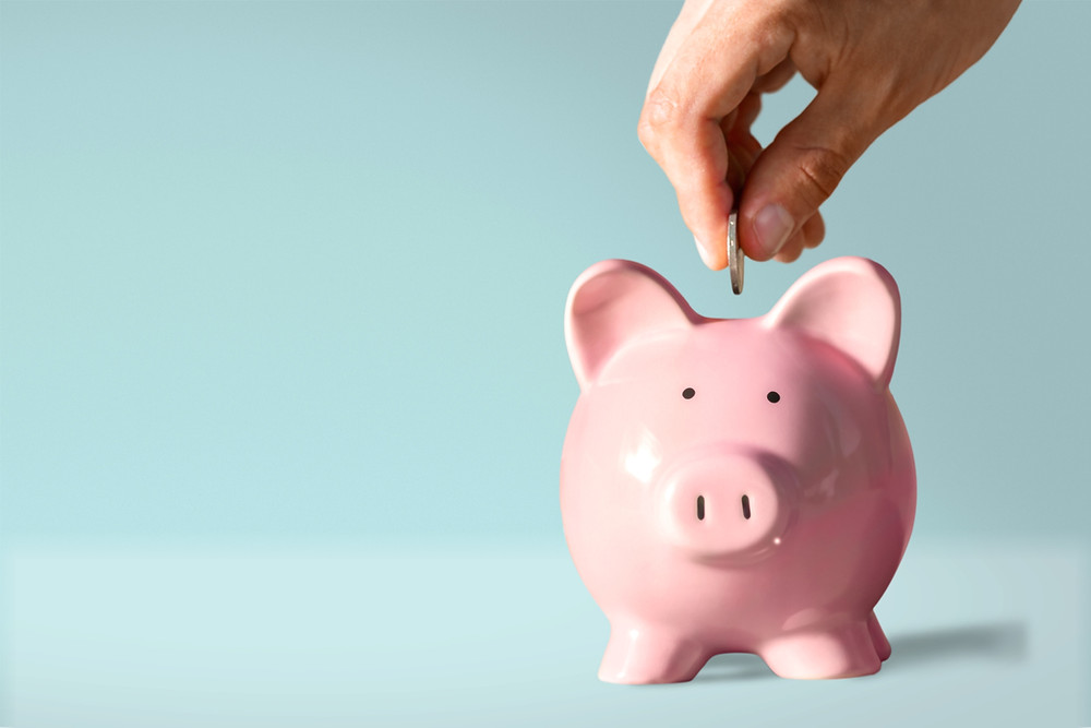 pink piggy bank with hand putting in a dollar