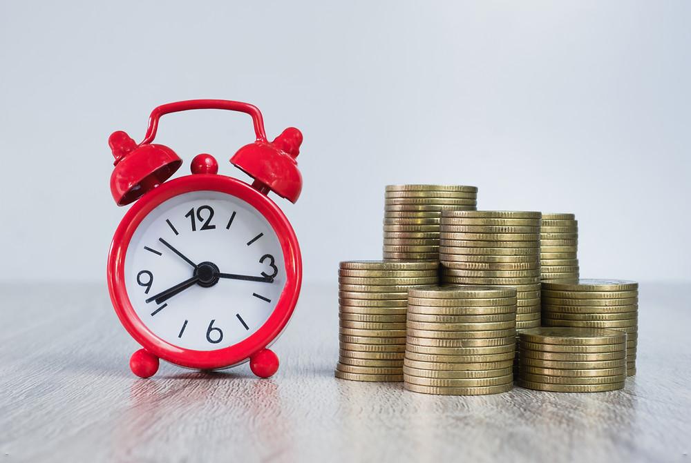 alarm clock next to coins