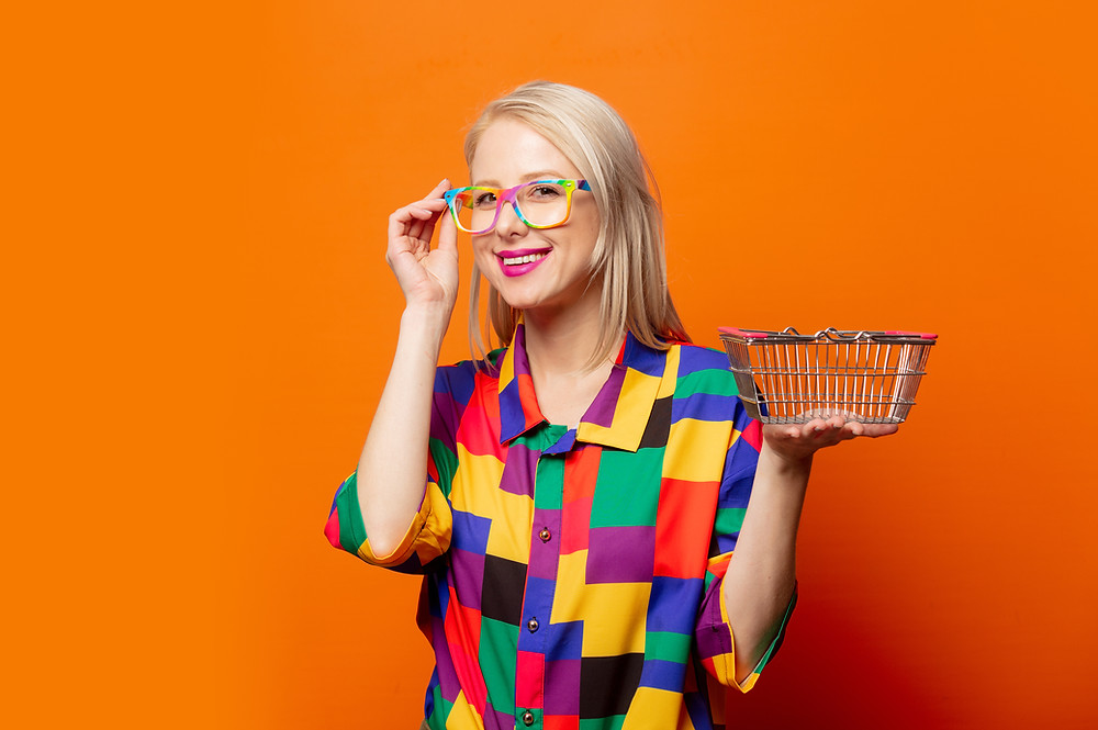 blonde woman in colourful shirt holding a shopping basket