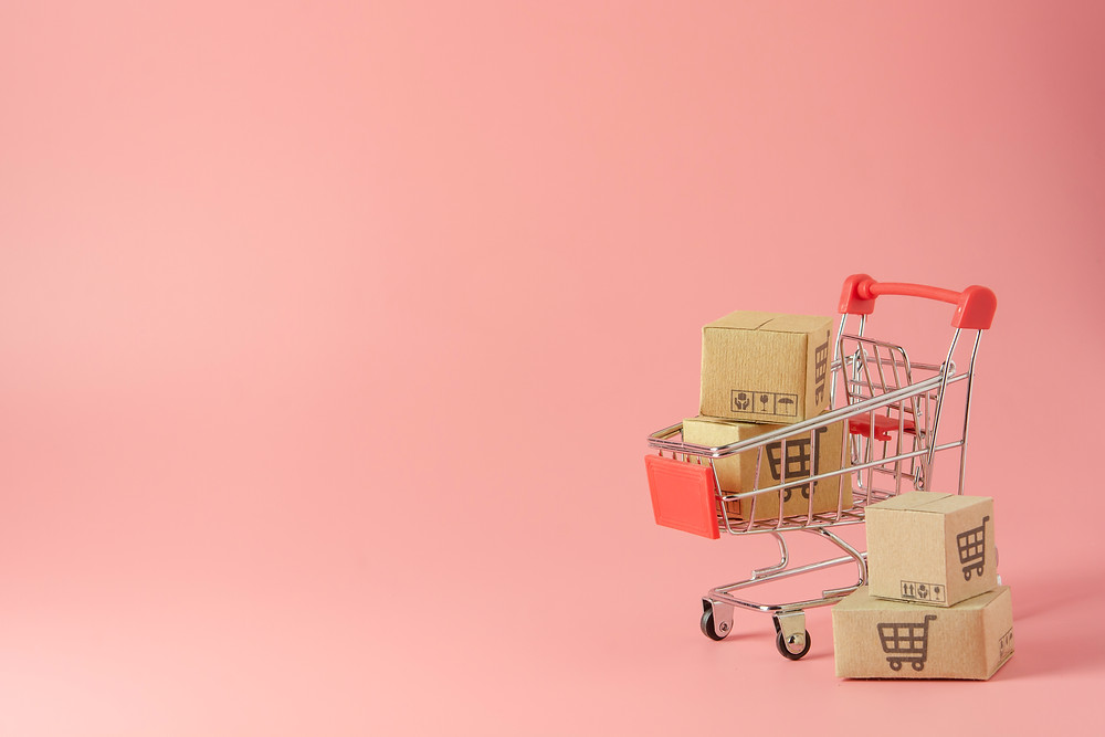 tiny cute shopping cart with small boxes on a pink background
