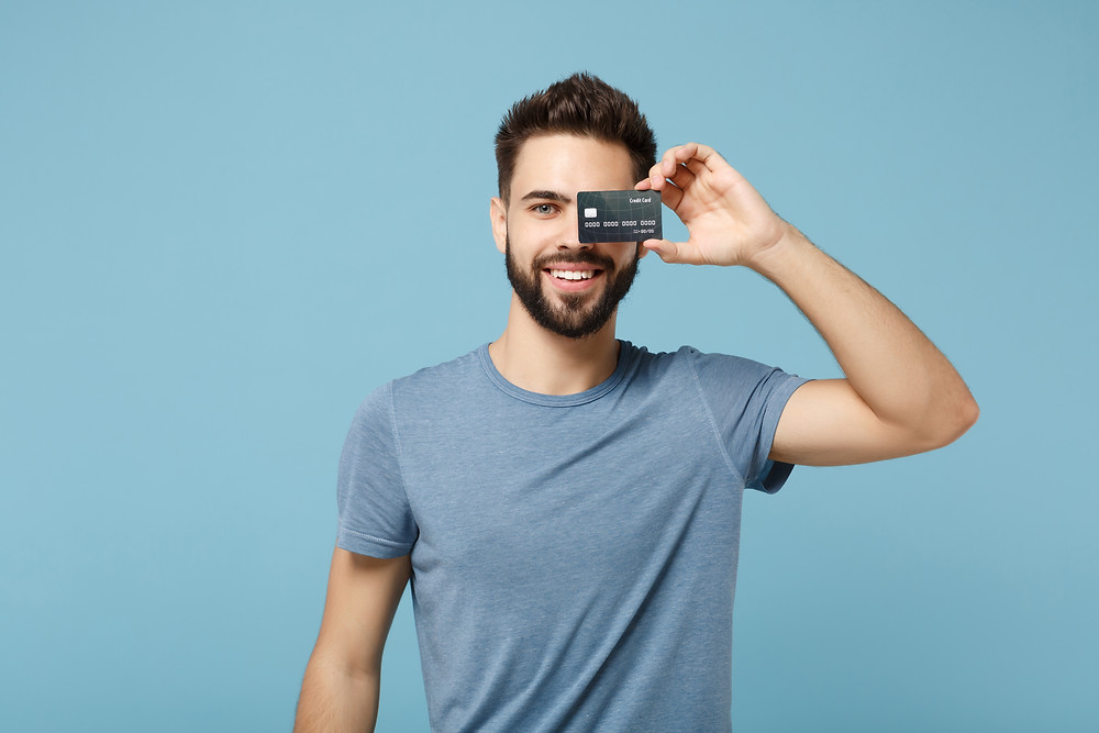 man holding credit card up to face