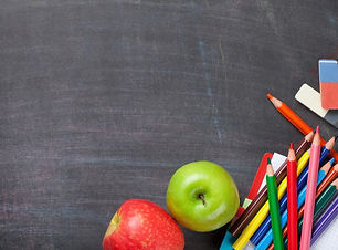 school-supplies-on-blackboard-background