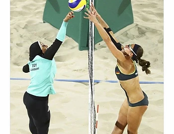 Two females of different ethnicities/nationalities playing volleyball.