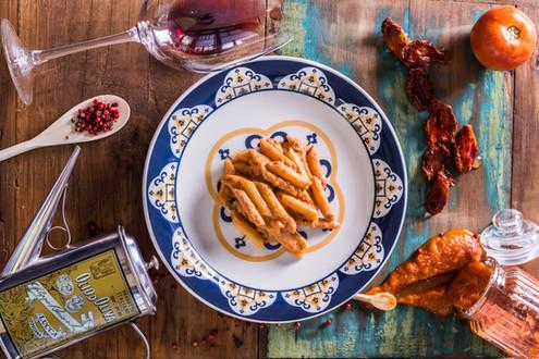 Penne ao molho de tomate seco. Mesa decorada com pedaços de tomate seco, tomate in natura, pimenta, azeite de oliva e taça de vinho tinto.