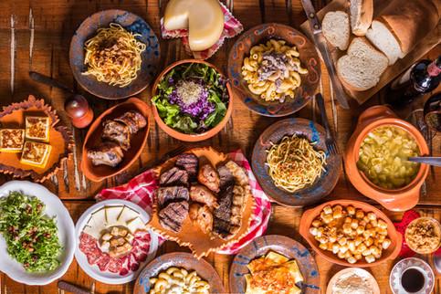 Culinária típica italiana. Mesa cheia, polenta na chapa, espaguete ao sugo, queijo de forma, pão colonial, nhoque, tortéi, sopa de capeletti, salada, galeto, picanha, salame e queijo.