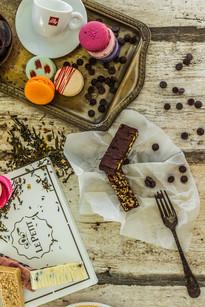 Confeitaria. Macaroons espalhados na mesa, com barra de chocolate caseira, xícara de café e gotas de chocolate.