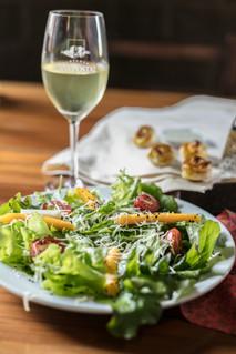 Salada verde cm taça de vinho branco.