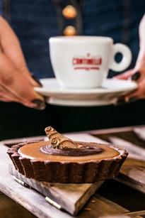 Confeitaria. Mousse de chocolate com xícara de café ao fundo.