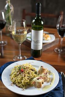 Spaghetti ao molho pesto com taça de vinho branco.