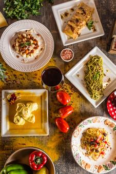 Culinária típica italiana. Mesa com massas, tomates, taça de vinho tinto, pimentões, tempeiros verdes.