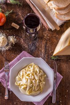 Culinária típica italiana. Prato de tagliatelle ao molho quatro queijos, na mesa com taça de vinho tinto, queijo parmesão, pão colonial, tomate.
