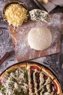 Pizza da pedra, ambientada com tabuleiro, massa de pizza, farinha e queijos