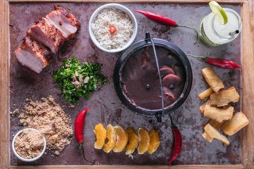 Feijoada completa, ambientada com arroz, carne de porco, farofa, pimenta, laranja, pão, e caipirinha.