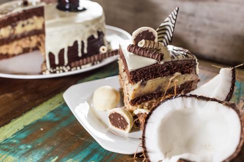 Confeitaria. Torta de coco com bombom. Decoração com chocolate, coco, bombom.