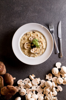 Alta Gastronomia. Risotto funghi com cogumelos espalhados ao redor do prato.