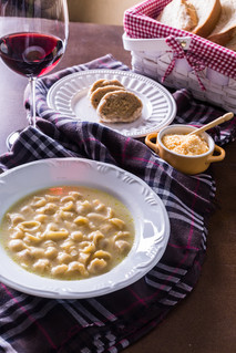 Culinária típica italiana. Sopa de capeletti, piem, queijo parmesão, taça de vinho tinto, pão colonial.
