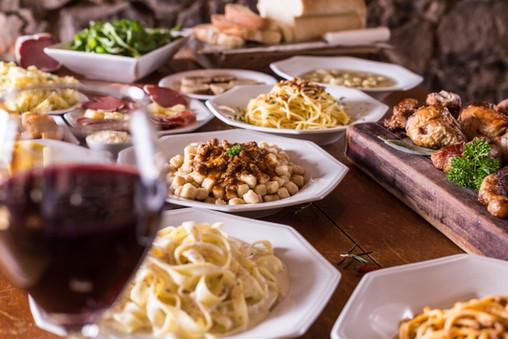 Culinária típica italiana. Mesa com tagliatelle ao molho quatro queijos, nhoque ao molho bolonhesa, espaghetti ao alho e óleo, tabuleiro com galeto, salada de radicci e taça de vinho tinto.