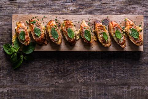 Alta Gastronomia. Bruschettas em uma tábua de madeira. Decoração com folhas de manjericão.