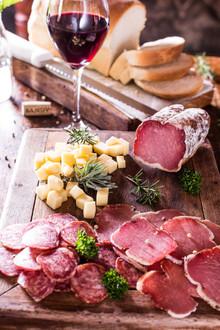 Culinária típica italiana. Tábua de frios. Copa, salame, queijo colonial, alecrim, pão colonial, taça de vinho tinto.