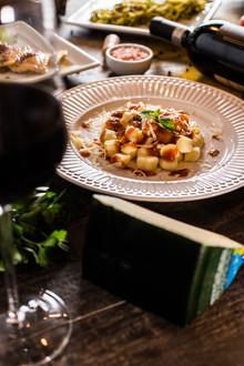 Culinária típica italiana. prato de nhoque com taça de vinho tinto.