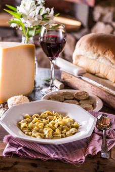 Culinária típica italiana. Sopa de capeletti, fatias de piem, queijo parmesão, pão colonial, taça de vinho tinto.