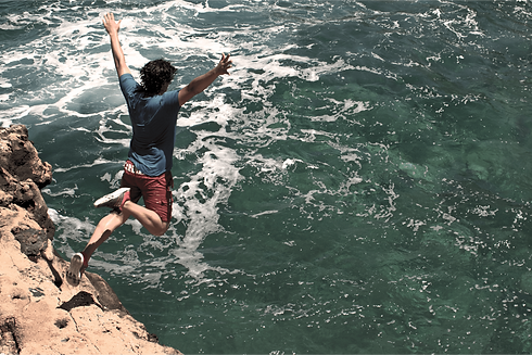 Man with dark hair jumping off a rock outcropping into a body of water below