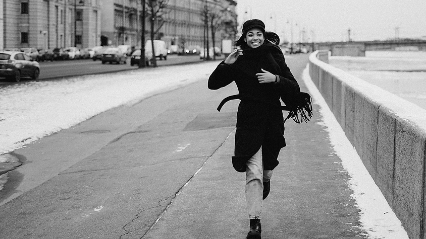 Woman running down a sidewalk with snow on the ground