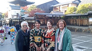 Customers with Japanese girls wearing traditional kimono in Kyoto, Japan during our Shades of Autumn small group tour of Japan.