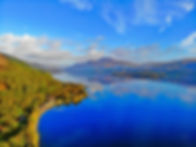 luxury tour of loch lomond with blue sky and mountains in scotland
