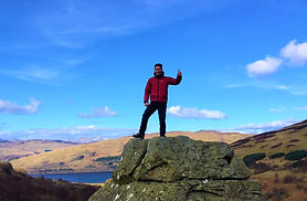 man on luxury private tous in scotland standing on a boulder giving thumbs up sign