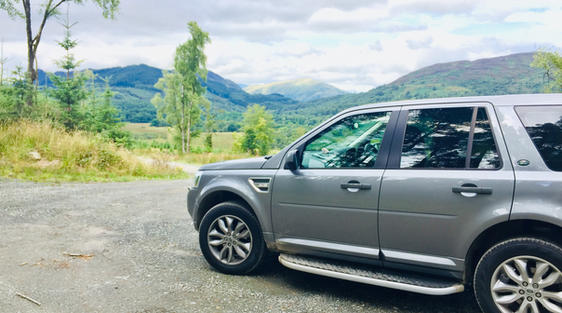 luxury private vehicle on tour off road in scotland near loch lomond with mountains and sky